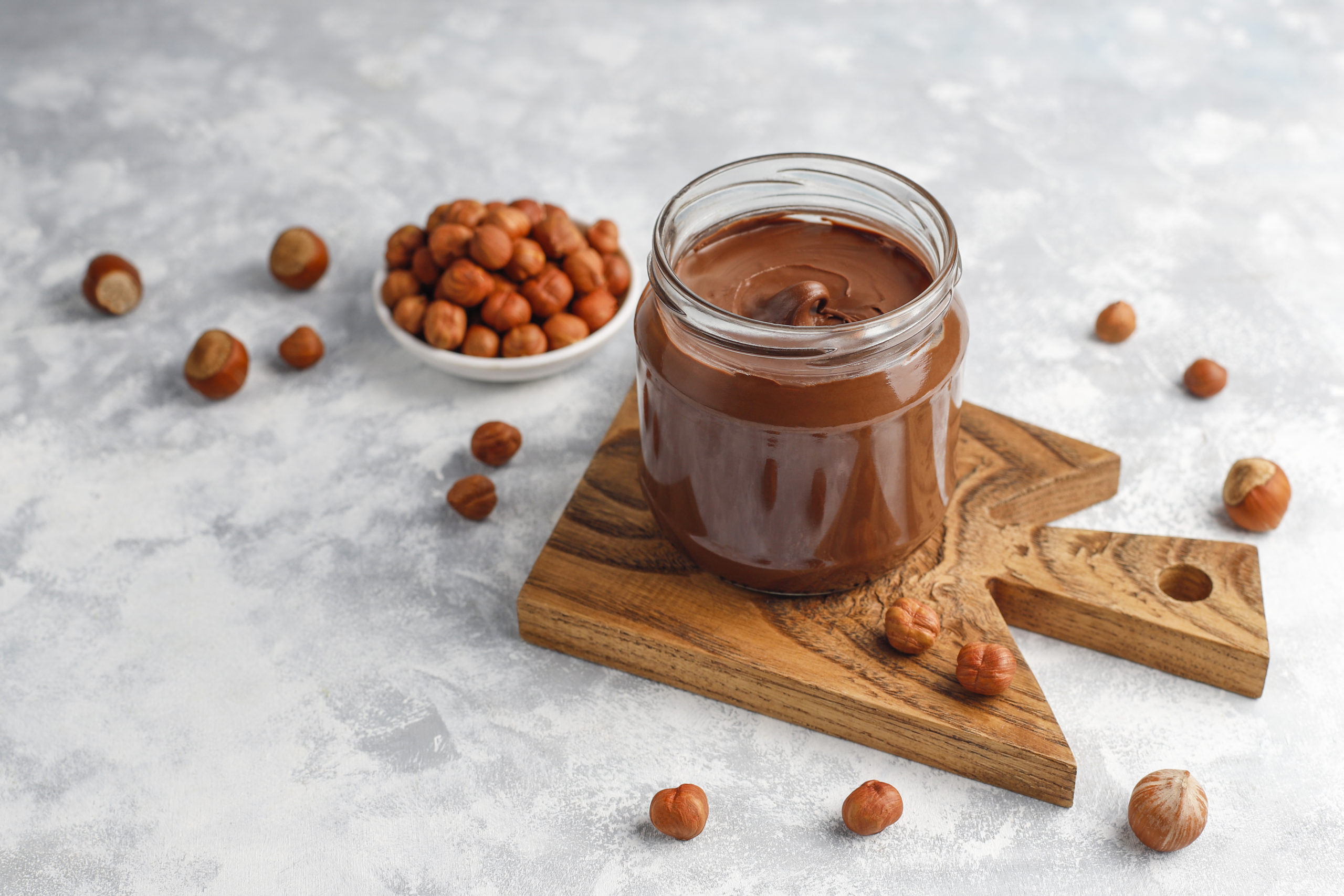 Chocolate spread or nougat cream with hazelnuts in glass jar on